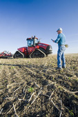 farmer using a tablet/tractor and air seeder planting winter wheat in a zero till field near Lorette, Manitoba, Canada