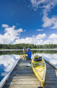 man sitting on dock next to his kayak while using a tablet, Two Mile Lake , Duck Mountain Provincial Park, Manitoba, Canada