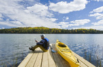 man sitting on dock next to his kayak while using a tablet, Spray Lake , Duck Mountain Provincial Park, Manitoba, Canada