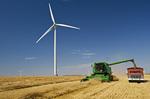 a combine empties wheat into a farm truck. Wind turbines are in the background, near St. Leon, Manitoba, Canada