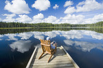man sitting in chair on dock using a tablet, Two Mile Lake , Duck Mountain Provincial Park, Manitoba, Canada