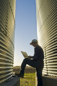 a farmer using a computer next to his grain storage bins