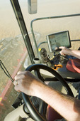 a farmer checks his combine monitor to evaluate crop data during the soybean harvest