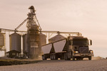 a farm truck/super B  leaves a farmer's grain storage facility during the harvest