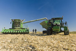 farmers talk next to a combine and tractor puling a grain wagon, during the feed corn harvest