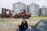 farm woman using a computer next to a Quadtrac tractor and grain storage bins
