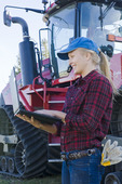 girl using a computer next to a Quadtrac tractor