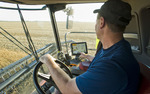 a farmer checks his combine monitor to evaluate crop data during the soybean harvest,