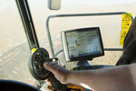 a farmer operates the controls of his combine during the soybean harvest,