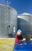 girl using a computer next to grain storage bins while a farmer climbs the bin in a farmyard, near Dugald, Manitoba