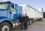 husband and wife  farmers next to farm truck in farmyard, near Dugald, Manitoba, Canada