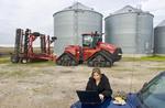 farm woman using a computer next to a Quadtrac tractor and grain storage bins