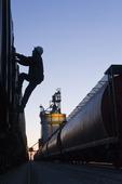 a worker climbs a grain rail hopper car at an inland grain terminal, Manitoba, Canada