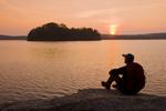 hiker on rocky shoreline, French Lake, Quietico Provincial Park,  Ontario, Canada
