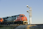 close-up of rail signal with approaching train in the background, near Winnipeg, Manitoba, Canada