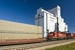 a train carrying containers passes a grain terminal, Grenfell, Saskatchewan Canada