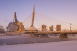 Winnipeg skyline from St. Boniface in winter showing the Red River,  Esplanade Riel Bridge and Canadian Museum for Human Rights,  Manitoba, Canada