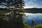 hiker along shoreline at Perch Lake , Duck Mountain Provincial Park, Manitoba, Canada