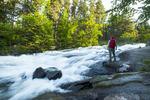 hiker along waterfalls, Rushing River Provincial Park near Kenora, Ontario, Canada