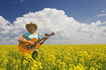 18 year old girl with guitar in a field of bloom stage canola,  Carey, Manitoba, Canada