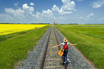 18 year old girl with guitar walking along railway with grain elevator in the background, Carey, Manitoba, Canada