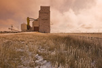 field with fence and old grain elevator, Aneroid, Saskatchewan, Canada