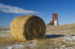 field with hay roll and old grain elevator, Cadillac, Saskatchewan, Canada
