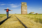 a man hikes along the railway with abandoned elevators in the background, Dankin, Saskatchewan, Canada