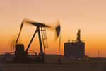 an oil pumpjack in wheat field with inland grain terminal in the background, near Gull Lake, Saskatchewan, Canada