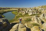 hiker along the Milk River, Writing On Stone Provincia Park, Alberta, Canada