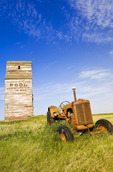 old tractor with abandoned elevator in the background, Dankin, Saskatchewan, Canada