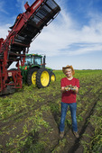 a girl holds potatoes. harvesting equipment in the background, near Holland, Manitoba, Canada