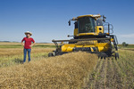 a teenage farm girl in front of a combine during the canola harvest, Tiger Hills,  Manitoba, Canada