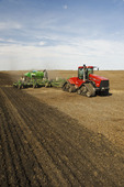 moving tractor and and air till seeder planting canola , near Lorette, Manitoba, Canada