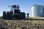 a man next to his tractor looks out over cultived farmland and grain storage bins near Lorette, Manitoba, Canada