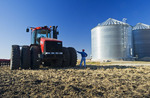 a man next to a  tractor pulling cultivating equipment loks out over a newly cultivted field with grain storage bins in the background, near Lorette, Manitoba, Canada