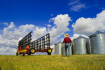 a man lwalks towards harrowing equipment next to grain storage bins, near Carey, Manitoba ,Canada