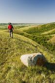 a hiker walks out over eroded hills, Qu´Appelle  River Valley,  Saskatchewan, Canada