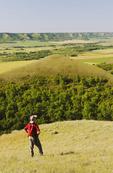 a hiker looks out over eroded hills, Qu´Appelle  River Valley,  Saskatchewan, Canada