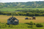 abandoned farm house and farm equipment harvesting hay, Qu'Appelle Valley, Saskatchewan, Canada
