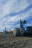 a man beside tractor and air till seeding equipment, near St. Agathe, Manitoba, Canada
