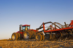 moving tractor and and air till seeder planting grain in canola stubble, near Dugald, Manitoba, Canada