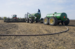 a farmer loads a seeder tank with canola seed and another tank with liquid fertilizer, near Dugald, Manitoba, Canada