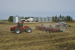 moving tractor and and air till seeder planting canola in wheat stubble, farmyard in the background, near Dugald, Manitoba, Canada