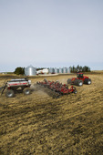 moving tractor and and air till seeder planting canola in grain stubble, near Dugald, Manitoba, Canada