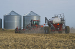 moving tractor and and air till seeder planting canola in wheat stubble, near Dugald, Manitoba, Canada