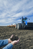a man examines soil with canola residue with tractor and air till seeding equipment in the background, near St. Agathe, Manitoba, Canada