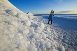 a man with snowshoes looks out over washed up ice piles, along Lake Winnipeg, Manitoba, Canada