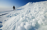 a man out over washed up ice piles, along Lake Winnipeg, Manitoba, Canada