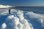 a photographer takes photos of washed up ice piles, along Lake Winnipeg, Manitoba, Canada